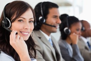 Zwei junge Frauen und ein junger Mann am Telefonieren, jeder von ihnen trägt ein Headset