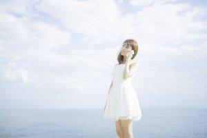 Junge Frau im weißen Kleid am Telefonieren durch Cloud-Telefonie, im Hintergrund sieht man das Meer
