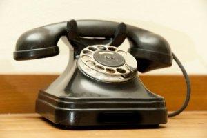 Sinnbild klassischer Telefonanlagen - ein schwarzes Retrotelefon mit Wählscheibe